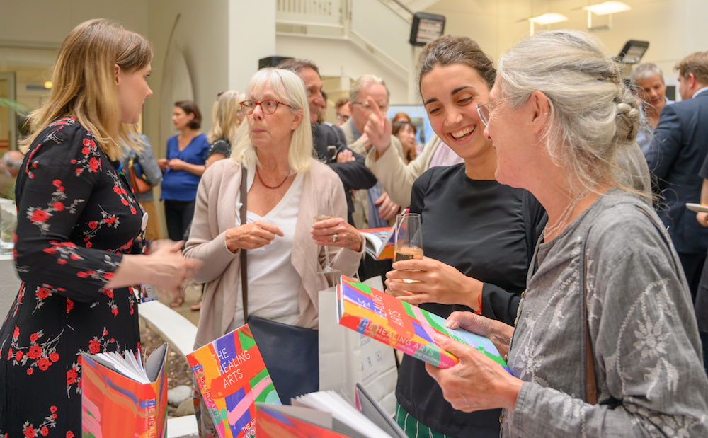 woman holding book at arts launch