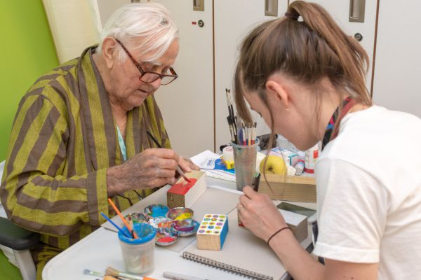 older male patient and female artist painting