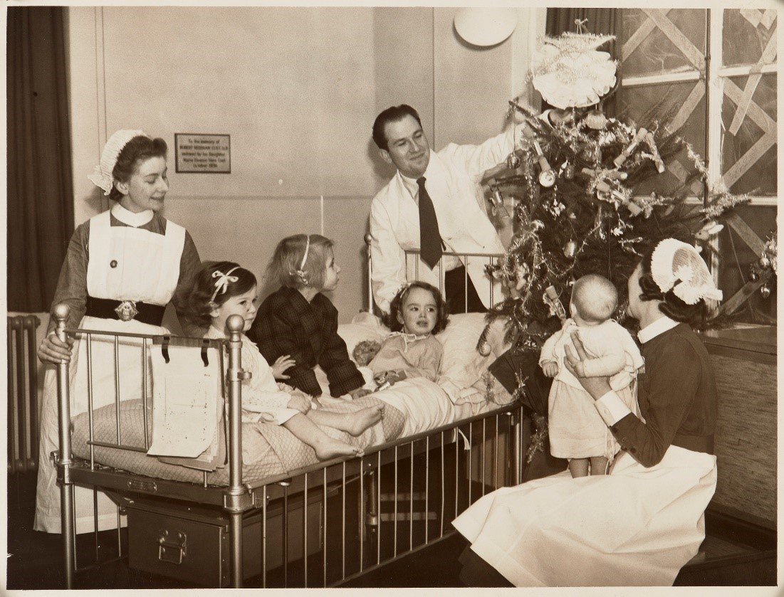 Doctor showing children a Christmas tree