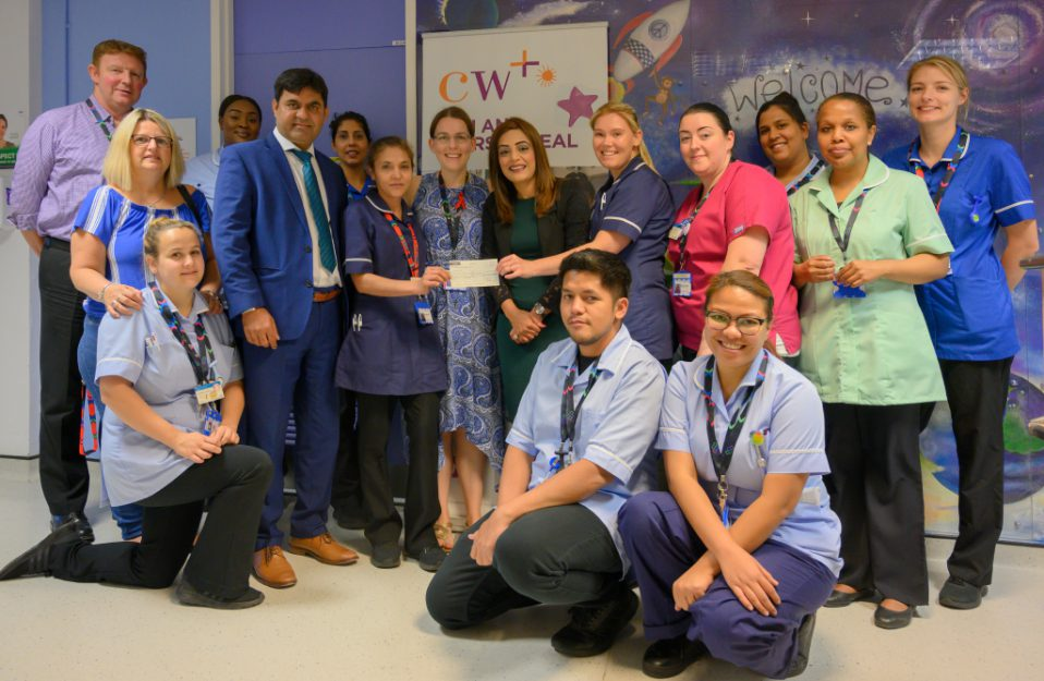 nhs staff group photo holding cheque