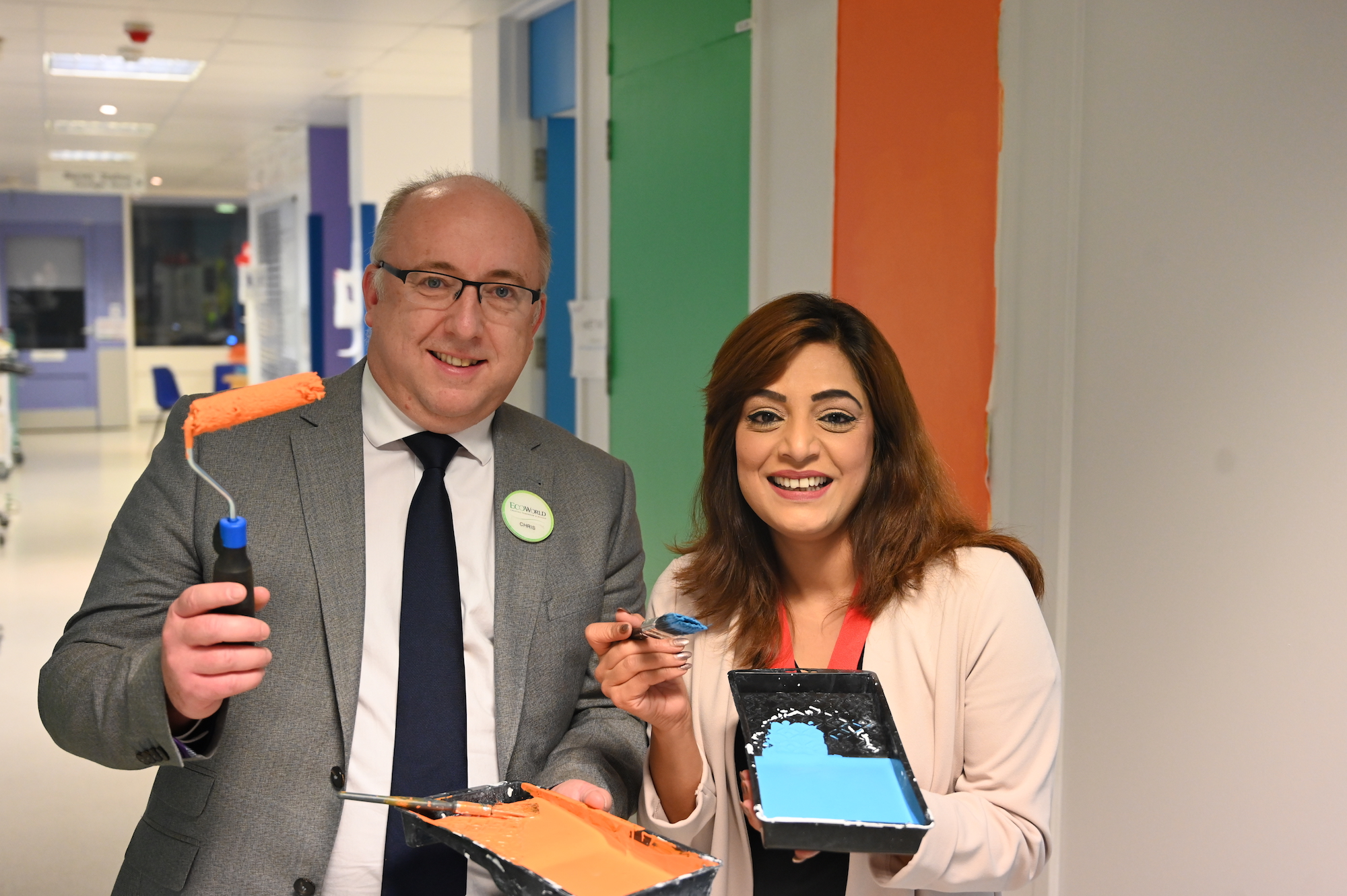 Chris Scott and Samia Chaudhary pose with paintbrushes