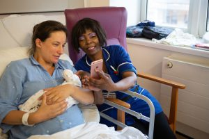New mother holding her baby, and nurse look at a maternity app on a mobile phone