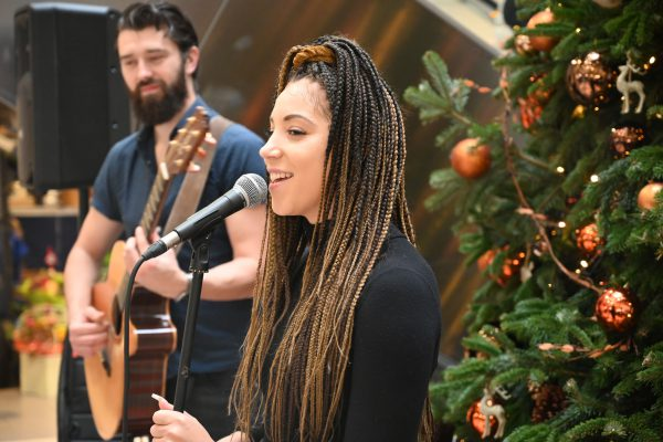 Young woman singing into microphone with guitarist and Christmas tree in background