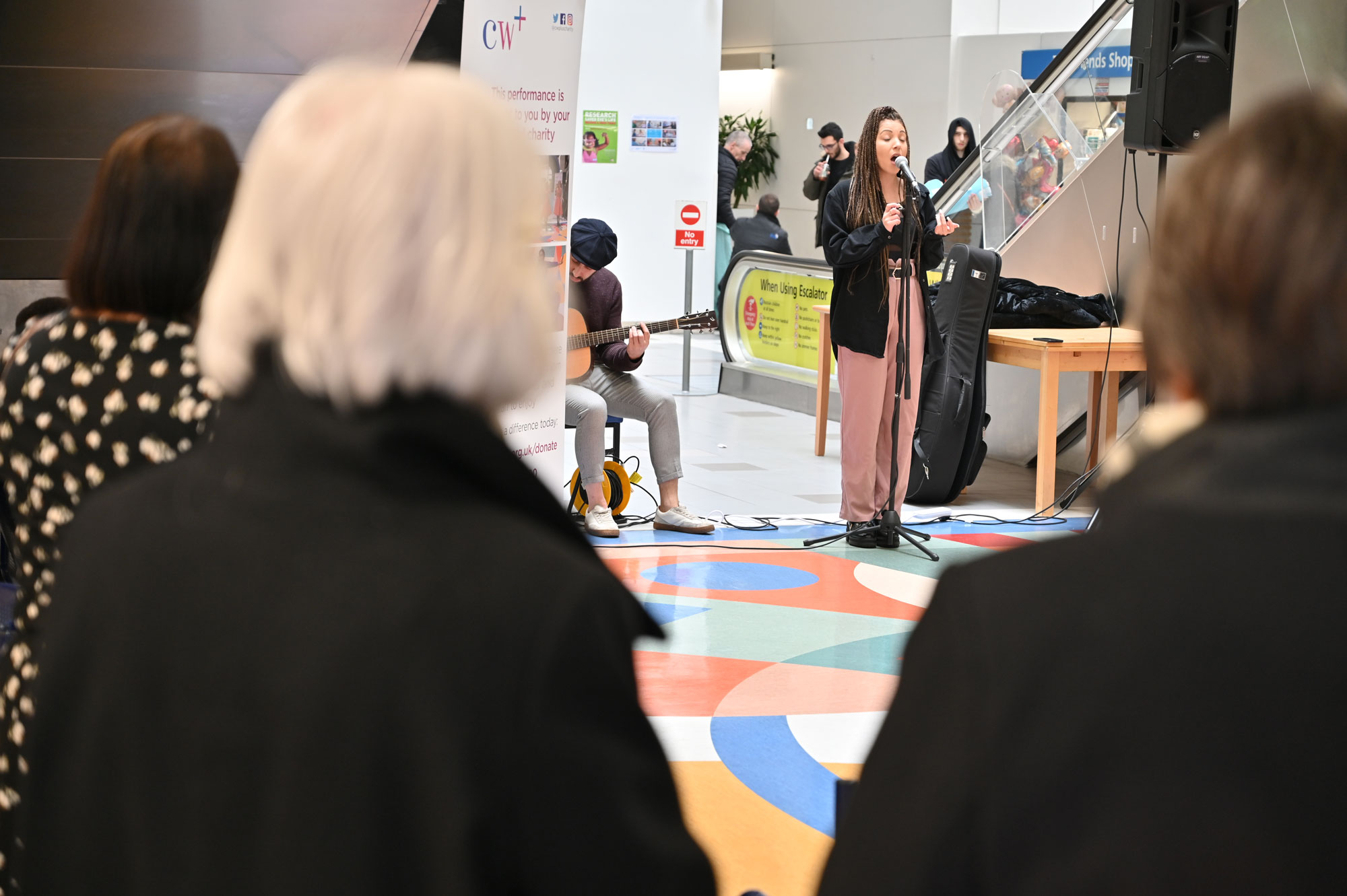 Young woman singing into microphone in a hospital atrium as visitors watch
