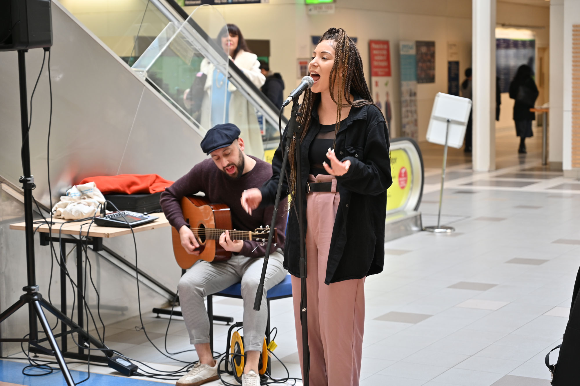 Young woman singing into microphone with man playing guitar in background